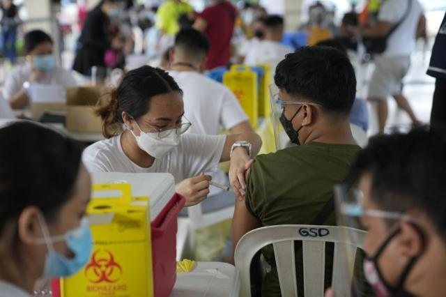 A man is inoculated with China's Sinovac COVID-19 vaccine in Quezon city, Philippines on Monday, Sept. 13, 2021. The government continues to urge Filipinos to get vaccinated as COVID-19 cases keep rising in the country. (AP Photo/Aaron Favila)