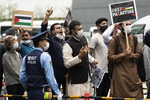 Muslims from different countries living in Japan chant slogans against the recent Israeli Palestinian conflict in Gaza after they marched to an area near the Israeli Embassy in Tokyo on Friday, May 21, 2021. (AP Photo/Hiro Komae)