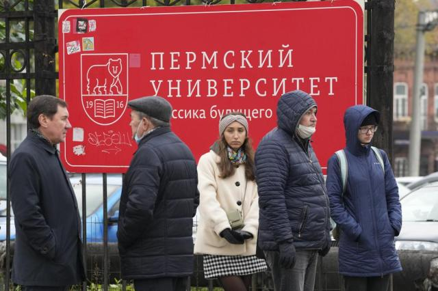 People stand outside the WLDPerm State University following a campus shooting in Perm, about 1,100 kilometers (700 miles) east of Moscow, Russia, Tuesday, Sept. 21, 2021. A student opened fire at the university, leaving a number of people dead and injured, before being shot in a crossfire with police and detained. Beyond saying that he was a student, authorities offered no further information on his identity or a possible motive. (AP Photo/Dmitri Lovetsky)