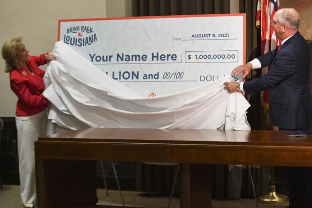 FILE - In this Thursday, June 17, 2021 file photo, first lady Donna Edwards, left, and Gov. John Bel Edwards, right, unveil a giant check during a news conference at the Louisiana State Capitol in Baton Rouge, La., to announce that Louisiana will participate in a lottery, giving cash prizes and scholarships to residents who have been vaccinated against the coronavirus. (Hilary Scheinuk/The Advocate via AP)