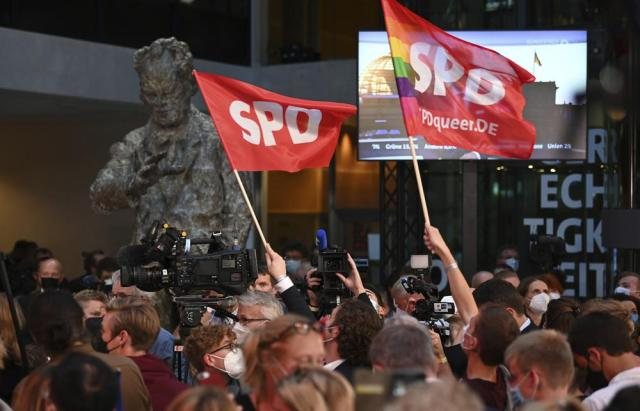 SPD supporters wave flags in front of the sculpture of Willy Brandt at the Willy Brandt House during the election party in Berlin, Sunday, Sept. 26, 2021. Exit polls show the center-left Social Democrats in a very close race with outgoing Chancellor Angela Merkel's bloc in Germany's parliamentary election, which will determine who succeeds the longtime leader after 16 years in power. (Britta Pedersen/dpa via AP)