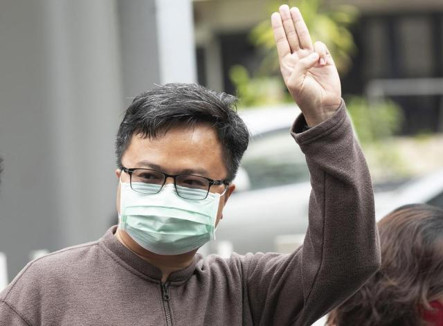 In this Tuesday, Feb. 9, 2021, photo, pro-democracy activist Arnon Nampha raises a three-fingered symbol of resistance at the criminal court in Bangkok, Thailand. A court in Thailand on Tuesday agreed to release Arnon, one of two key leaders of the anti-government protest movement, on bail on the condition that he refrains from activities deemed to defame the monarchy. Arnon must also wear electronic tags and are banned from leaving the country. (AP Photo/Sakchai Lalit)