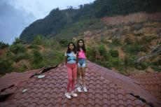 Las gemelas Dulce Alejandra y Génesis Mejía, de 12 años, posan para un retrato en el techo de una de las casas dañadas tras el paso de los huracanes Eta e Iota en la comunidad de La Reina, Honduras, el sábado 26 de junio de 2021. (AP Foto/Rodrigo Abd)