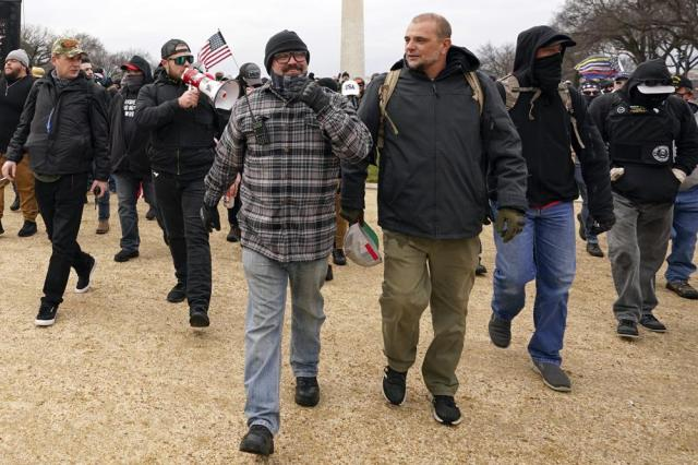 FILE - In this Jan. 6, 2021, file photo, Proud Boys including Joseph Biggs, front left, walks toward the U.S. Capitol in Washington, in support of President Donald Trump. With the megaphone is Ethan Nordean, second from left. Outside pressures and internal strife are roiling two far-right extremist groups after members were charged in the attack on the U.S. Capitol. Former President Donald Trump's lies about a stolen 2020 election united an array of right-wing supporters, conspiracy theorists and militants on Jan. 6.  (AP Photo/Carolyn Kaster, file)