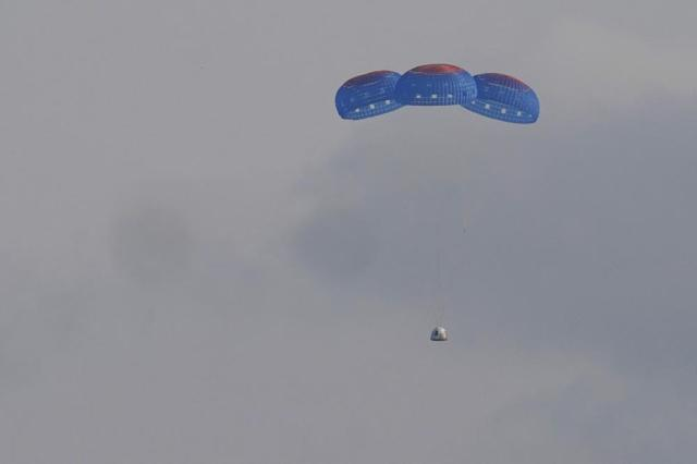 Blue Origin's New Shepard capsule parachutes safely down to the launch area with passengers Jeff Bezos, founder of Amazon and space tourism company Blue Origin, brother Mark Bezos, Oliver Daemen and Wally Funk, near Van Horn, Texas, Tuesday, July 20, 2021. (AP Photo/Tony Gutierrez)