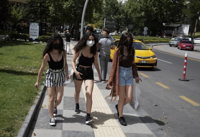 Young women walk along a street as a temperature of 36 degrees celsius hits the Turkish capital, Ankara, Friday, July 2, 2021. Turkish health-care workers and people aged over 50 has started to get a third dose of vaccines, Pfizer-BioNTech or China's Sinovac.( Photo/Burhan Ozbilici)