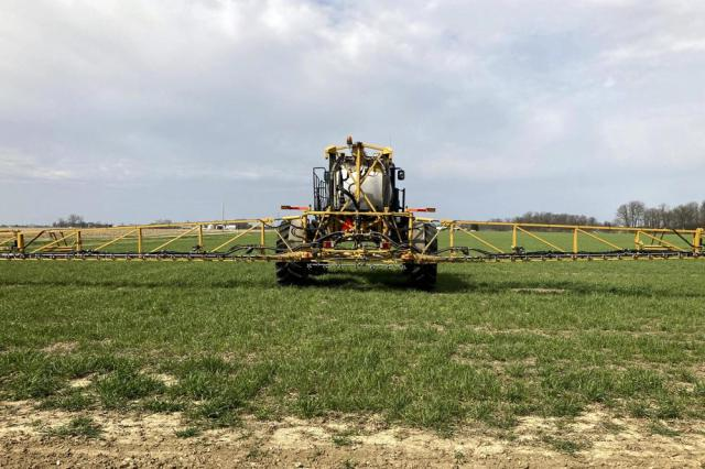 Farmer Rick Clifton drives a spray tractor across one of his fields, applying herbicide to cover crops that occupied the ground during fall and winter in Orient, Ohio, on April 5, 2021. Clifton grows cereal rye and rapeseed to prevent erosion and make the ground healthier for his corn, soybean and wheat cash crops. Cover crops store carbon in the soil, keeping the greenhouse gas out of the atmosphere. (AP Photo/John Flesher)