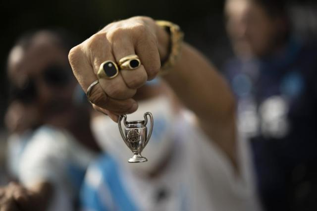 A Marseille supporter displays a Champions League Cup figurine with the Olympique de Marseille logo, outside the Orange Velodrome stadium in Marseille, southern France, Sunday, Oct. 3, 2021. Bernard Tapie, the charismatic president of French soccer club Marseille during its glory era whose reign was marred by a match-fixing scandal, has died, Sunday. He was 78. (AP Photo/Daniel Cole)