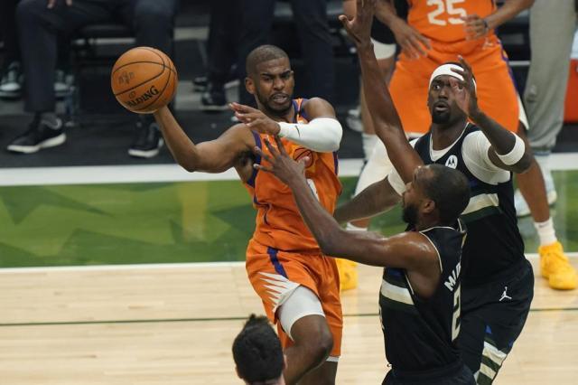 Phoenix Suns guard Chris Paul tries to pass around Milwaukee Bucks forward Khris Middleton during the first half of Game 6 of basketball's NBA Finals in Milwaukee, Tuesday, July 20, 2021. (AP Photo/Paul Sancya)