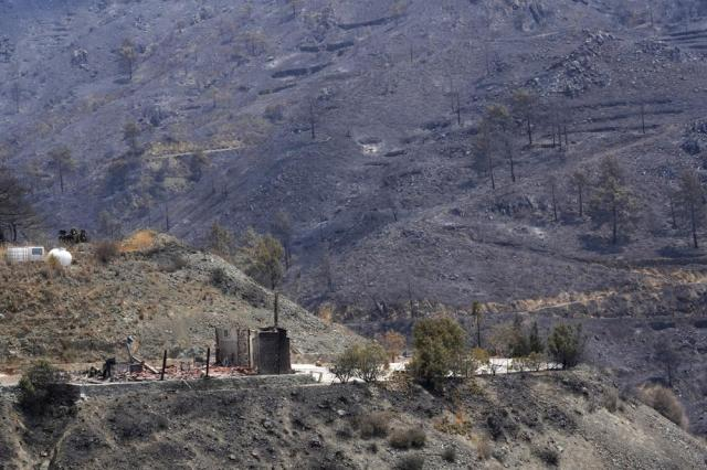 """A burned house is seen on Troodos mountain, in Ora village, southwestern Cyprus, Sunday, July 4, 2021. Cyprus search crews discovered the bodies of four people outside a fire-swept mountain village on Sunday in what a government minister called the """"most destructive"""" blaze in the east Mediterranean island nation's history. (AP Photo/Petros Karadjias)"""