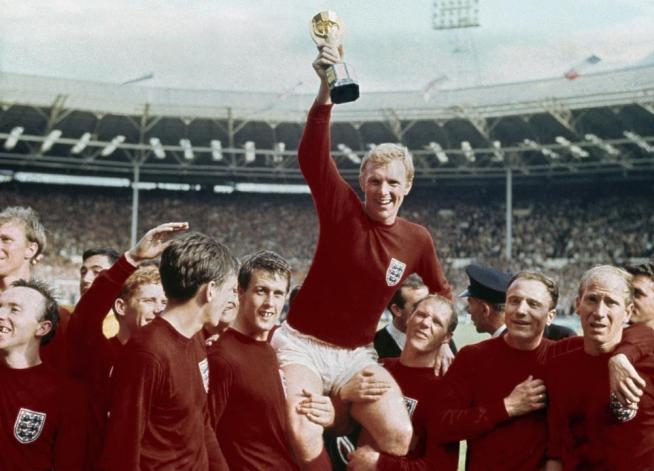FILE - In this July 30, 1966 file photo, England's soccer captain Bobby Moore, center, is carried by teammates Geoff Hurst, center left, and Ray Wilson as he holds World Cup after England defeated Germany 4-2 in the final at London's Wembley Stadium. (AP Photo, file)