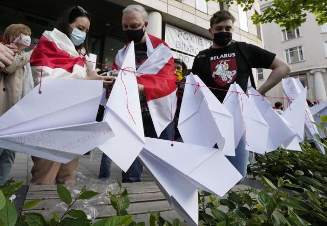 Protesters attach paper planes during a demonstration of Belarusians living in Poland and Poles supporting them in front of European Commission office in Warsaw demanding freedom for Belarus opposition activist Raman Protasevich in Warsaw, Poland, Monday, May 24, 2021. Western outrage grew and the European Union threatened more sanctions Monday against Belarus over its forced diversion of a passenger jet to the capital of Minsk in order to arrest opposition journalist Raman Protasevich in a dramatic gambit that some said amounted to state terrorism or piracy. (AP Photo/Czarek Sokolowski)