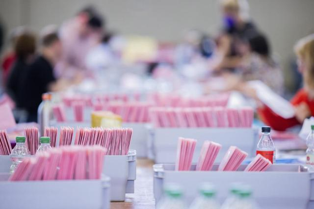 Election workers open the pink envelopes during the counting of the postal vote for the Germany parliament election, in Cologne, Germany, Sunday, Sept. 26, 2021. German voters are choosing a new parliament in an election that will determine who succeeds Chancellor Angela Merkel after her 16 years at the helm of Europe's biggest economy. (Rolf Vennenbernd/dpa via AP)