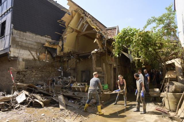 Helpers work in the streets of Dernau, in Rhineland-Palatinate, Germany, Wednesday, July 21, 2021. The severe flooding has made numerous houses here uninhabitable. (Thomas Frey/dpa via AP)