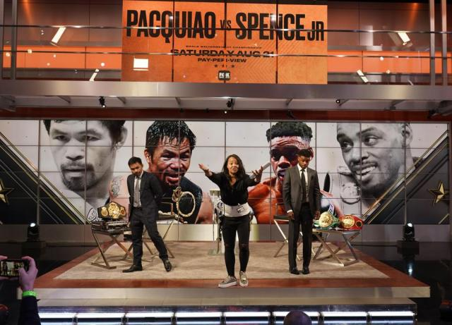 Fox Sports stage manager Carrie Snow, middle, directs the start of a live broadcast of a news conference with boxers Manny Pacquiao, left, and Errol Spence Jr., at the Fox Studios lot in Los Angeles, Sunday, July 11, 2021. (AP Photo/Damian Dovarganes)