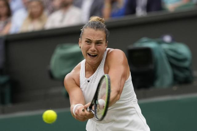 Aryna Sabalenka of Belarus plays a return during the women's singles quarterfinals match against Tunisia's Ons Jabeur on day eight of the Wimbledon Tennis Championships in London, Tuesday, July 6, 2021. (AP Photo/Kirsty Wigglesworth)