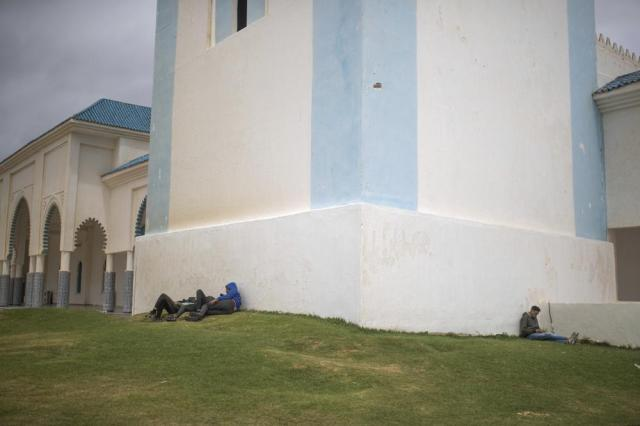 Would-be migrants take shelter near a mosque as they wait for a chance to cross to the Spanish enclave of Ceuta from the northern town of Fnideq, Morocco, Thursday, May 20, 2021. An extraordinary surge of migrants seeking to leave Morocco for Spain this week has left the border town suffering under the strain. (AP Photo/Mosa'ab Elshamy)