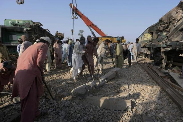 Railway workers rebuild the track at the site of a train collision in the Ghotki district, southern Pakistan, Tuesday, June 8, 2021. The death toll from a deadly train accident in southern Pakistan jumped to dozens on Tuesday after rescuers pulled a dozen more bodies from crumpled cars of two trains that collided on a dilapidated railway track a day ago, an official said, as rescue work continued even 24 hours after the incident to find any survivors. (AP Photo/Fareed Khan)