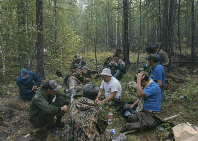 Volunteers rest as they dig a firebreak moat to stop a forest fire outside Magaras village 87 km. (61 miles) west of Yakustk, the capital of the republic of Sakha also known as Yakutia, Russia Far East, Sunday, July 18, 2021. Russia has been plagued by widespread forest fires, blamed on unusually high temperatures and the neglect of fire safety rules, with the Sakha-Yakutia region in northeastern Siberia being the worst affected. (AP Photo/Alexey Vasilyev)
