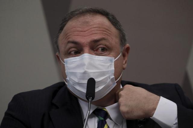 Eduardo Pazuello, exministro de Salud de Brasil, se acomoda el cuello el miércoles 19 de mayo de 2021 durante su testimonio ante el Senado que investiga la actuación del gobierno frente a la pandemia de COVID-19, en Brasilia, Brasil. (AP Foto/Eraldo Peres)