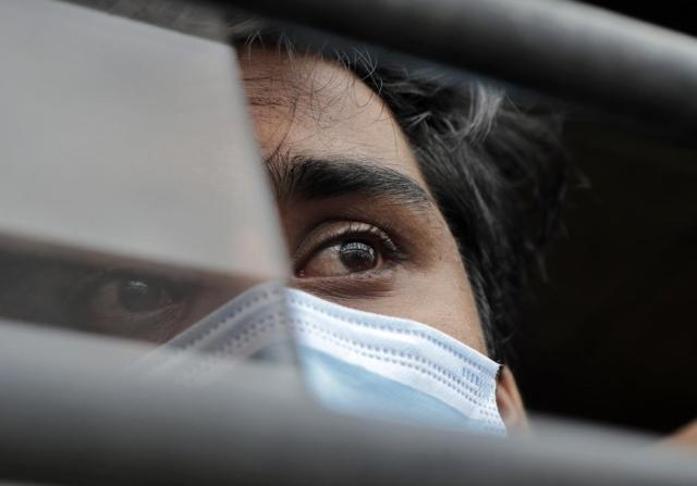 A man rescued by the Indian navy from a barge that sank in the Arabian sea and brought by Indian naval ship INS Kochi looks on as he sits inside a vehicle in Mumbai, India, Wednesday, May 19, 2021. The barge carrying personnel deployed for offshore drilling sank off Mumbai as a deadly cyclone blew ashore this week. (AP Photo/Rajanish Kakade)