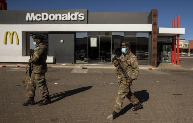 Soldiers patrol at a shopping centre in Soweto, Johannesburg, Tuesday July 13, 2021. South Africa's rioting continued Tuesday with the death toll rising to 32 as police and the military struggle to quell the violence in Gauteng and KwaZulu-Natal provinces. The violence started in various parts of KwaZulu-Natal last week when Zuma began serving a 15-month sentence for contempt of court. (AP Photo/Themba Hadebe)
