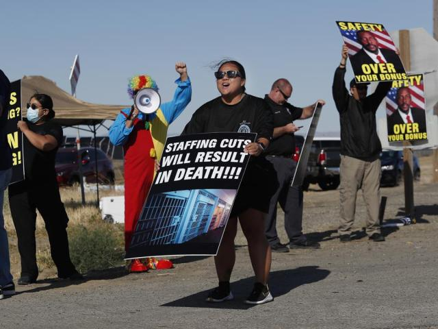 Noni Ahulau, from Honolulu, along with others, protests staffing shortages at the Federal Correctional Institution at Mendota, Monday, May 17, 2021, near the facility, in Mendota, Calif. The signs being displayed and held, at right, show a picture of FCI Mendota Warden Douglas K. White. (AP Photo/Gary Kazanjian)