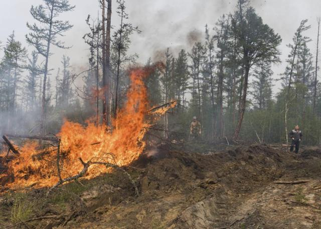 Volunteers and employees of the Yakutlesresurs extinguish a forest fire outside Magaras village 87 km. (61 miles) west of Yakustk, the capital of the republic of Sakha also known as Yakutia, Russia Far East, Sunday, July 18, 2021. Russia has been plagued by widespread forest fires, blamed on unusually high temperatures and the neglect of fire safety rules, with the Sakha-Yakutia region in northeastern Siberia being the worst affected. (AP Photo/Alexey Vasilyev)