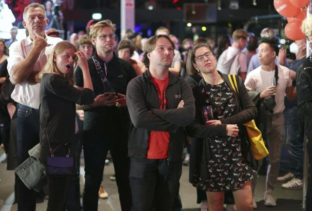 Guests at the election party of Die Linke react at the Karl-Liebknecht-Haus after the publication of the first forecasts on the outcome of the 2021 federal election, in Berlin Sunday, Sept. 26, 2021. Exit polls show the center-left Social Democrats in a very close race with outgoing Chancellor Angela Merkel's bloc in Germany's parliamentary election, which will determine who succeeds the longtime leader after 16 years in power.  (Jan Woitas/dpa via AP)