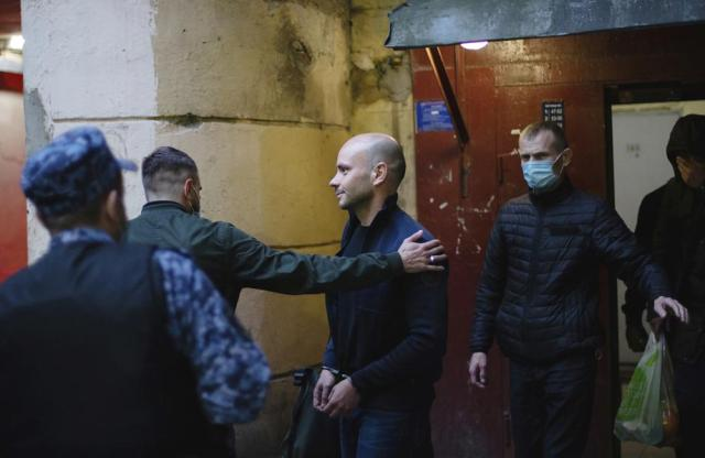 Andrei Pivovarov, the head of Open Russia movement that dissolved itself last week, is taken from his apartment building after being arrested in St.Petersburg, Russia, Tuesday, June 1, 2021. Russian authorities are ramping up their pressure on dissent ahead of the country's parliamentary election, arresting one opposition activist and raiding several others' homes. Pivovarov has been pulled off a plane at St. Petersburg's airport and is to be taken to Krasnodar in southern Russia. (Ruslan Terekhov/SOTA via AP)