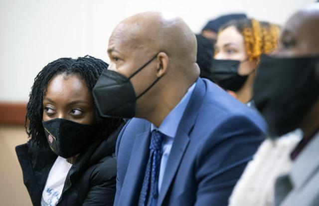 Monet Carter-Mixon, left, the sister of Manuel Ellis, sits with family members and attorney James Bible as they watch the Pierce County Superior Court arraignment appearances of three Tacoma police officers, Friday, May 28, 2021 in Tacoma, Wash. Three Washington state police officers pleaded not guilty Friday in the death of Manuel Ellis, another Black man who pleaded for breath under an officer's knee. (Tony Overman/The News Tribune via AP, Pool)