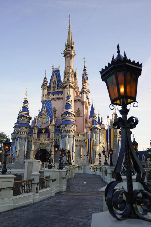 The newly painted Cinderella Castle at the Magic Kingdom at Walt Disney World is seen with the the crest to celebrate the 50th anniversary of the theme park Monday, Aug. 30, 2021, in Lake Buena Vista, Fla. (AP Photo/John Raoux)