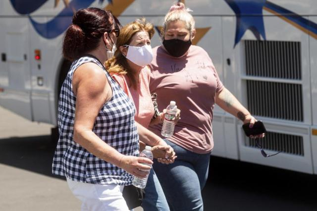 Women leave a gathering area for Santa Clara Valley Transportation Authority (VTA) workers and family members following a shooting at one of the agency's rail yards on Wednesday, May 26, 2021, in San Jose, Calif. A Santa Clara County sheriff's spokesman said a shooting at the rail yard left at least eight people, including the gunman, dead. (AP Photo/Noah Berger)