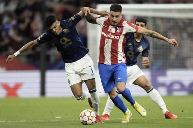 Atletico Madrid's Jose Gimenez, center, challenges for the ball with Porto's Luis Diaz, left, and Porto's Mehdi Taremi during the Champions League Group B soccer match between Atletico Madrid and Porto at Wanda Metropolitano stadium in Madrid, Spain, Wednesday, Sept. 15, 2021. (AP Photo/Manu Fernandez)