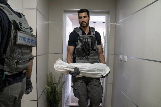 A technician removes an unexploded missile fired from the Gaza Strip that landed on the top floor of a high rise apartment building, Thursday, May 20, 2021, in Ashkelon, southern Israel. (AP Photo/John Minchillo)