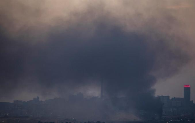 Smoke covers the Johannesburg skyline as people protest in the downtown area of Johannesburg, South Africa, Sunday, July 11, 2021. Protests have spread from the KwaZulu Natal province to Johannesburg against the imprisonment of former South African President Jacob Zuma who was imprisoned last week for contempt of court. (AP Photo/Themba Hadebe)