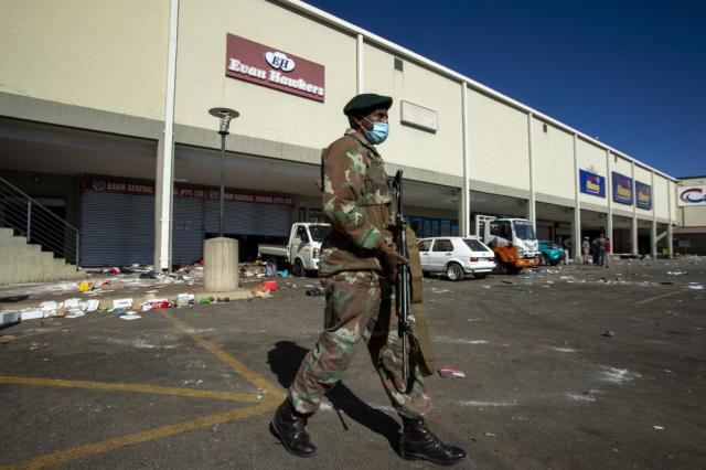 A soldiers patrol at a shopping centre in Soweto, Johannesburg Tuesday July 13, 2021. South Africa's rioting continued Tuesday with the death toll rising to 32 as police and the military struggle to quell the violence in Gauteng and KwaZulu-Natal provinces. The violence started in various parts of KwaZulu-Natal last week when Zuma began serving a 15-month sentence for contempt of court. (AP Photo/Themba Hadebe)