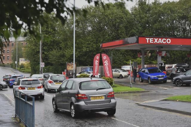 Cars queue at a petrol station in Stalybridge, England, Saturday Sept. 25, 2021. The haulage industry says the U.K. is short tens of thousands of truckers, due to a perfect storm of factors including the coronavirus pandemic, an aging workforce and an exodus of European Union workers following Britain's departure from the bloc. BP and Esso shut a handful of their gas stations this week, and motorists have formed long lines as they try to fill up in case of further disruption. (Anthony Devlin/PA via AP)