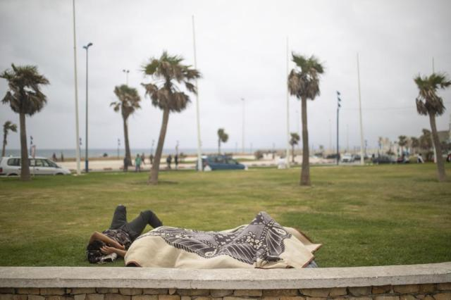 Would-be migrants sleep in a roundabout on the street as they wait for a chance to cross to the Spanish enclave of Ceuta from the northern town of Fnideq, Morocco, Thursday, May 20, 2021. An extraordinary surge of migrants seeking to leave Morocco for Spain this week has left Fnideq suffering under the strain. (AP Photo/Mosa'ab Elshamy)