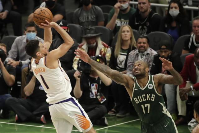 Phoenix Suns' Devin Booker (1) shoots against Milwaukee Bucks' P.J. Tucker (17) during the second half of Game 3 of basketball's NBA Finals, Sunday, July 11, 2021, in Milwaukee. (AP Photo/Aaron Gash)