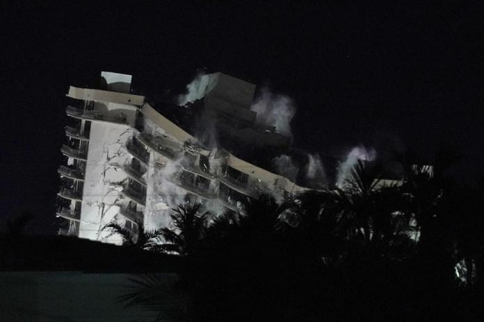 Demolition teams bring down the unstable remainder of the Champlain Towers South condo building, late Sunday, July 4, 2021, in Surfside, Fla. The work to demolish the remains had suspended the search-and-rescue mission, but officials said Sunday it should eventually open up new areas for rescue teams to explore. (AP Photo/Wilfredo Lee)