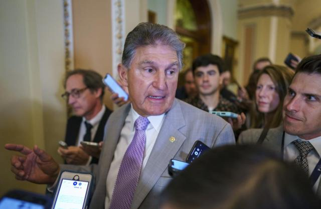 Sen. Joe Manchin, D-W.Va., a key negotiator in the infrastructure talks, is surrounded by reporters as walks through the Capitol in Washington, Tuesday, July 13, 2021. (AP Photo/J. Scott Applewhite)