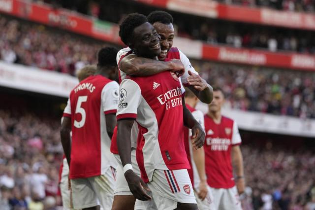Arsenal's Bukayo Saka, center, celebrates after scoring his side's third goal during the English Premier League soccer match between Arsenal and Tottenham Hotspur at the Emirates stadium in London, Sunday, Sept. 26, 2021. (AP Photo/Frank Augstein)
