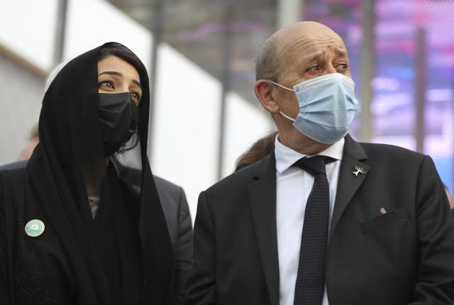 French Foreign Affairs Minister Jean-Yves Le Drian, right, and Reem Ebrahim Al-Hashimi, Minister of State and Managing Director for the Dubai World Expo 2020, watch the. Patroille de France aerobatic team flying over the French Pavilion at the Dubai Expo 2020 in Dubai, United Arab Emirates, Saturday, Oct. 2, 2021. (AP Photo/Kamran Jebreili)