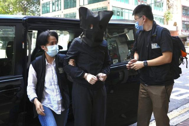 A hooded suspect is accompanied by police officers to search evidence at office in Hong Kong Thursday, July 22, 2021. Hong Kong's national security police on Thursday arrested five people from a trade union of the General Association of Hong Kong Speech Therapists on suspicion of conspiring to publish and distribute seditious material, in the latest arrests made amid a crackdown on dissent in the city. (AP Photo/Vincent Yu)