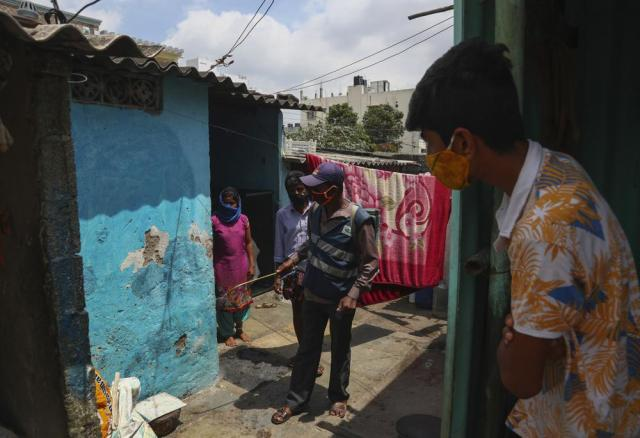 A municipal worker disinfects a slum area as a precautionary measure against COVID-19 in Hyderabad, India, Thursday, May 20, 2021. India has the second-highest coronavirus caseload after the U.S. with more than 25 million confirmed infections. (AP Photo/Mahesh Kumar A.)