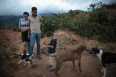 Nery Flores, de 22 años, y su esposa Ada Castrón, de 19, acuden con su hijo Daniel, de 3, al lugar donde estuvo su casa antes de quedar destruída por un deslave provocado por el paso de los huracanes Eta e Iota en la comunidad de La Reina, Honduras, el sábado 26 de junio de 2021. (AP Foto/Rodrigo Abd)