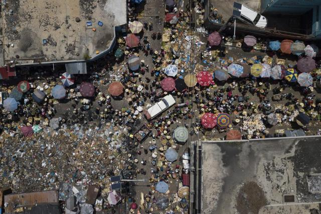People shop at Petion-Ville market in Port-au-Prince, Haiti, Sunday, July 11, 2021, four days after the assassination of Haitian President Jovenel Moise. (AP Photo/Matias Delacroix)