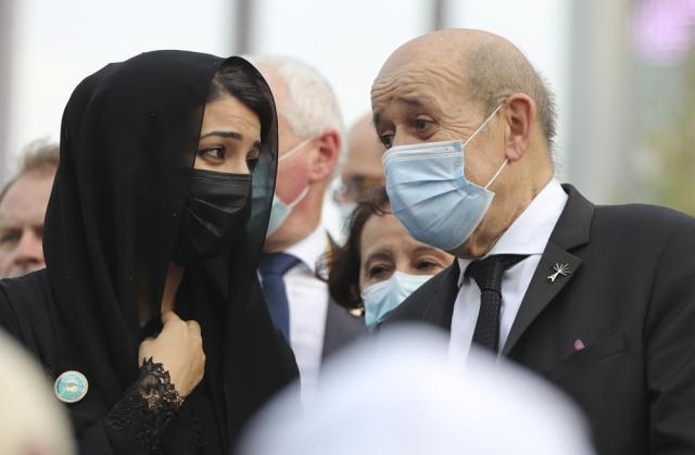 French Foreign Affairs Minister Jean-Yves Le Drian, right, and Reem Ebrahim Al-Hashimi, Minister of State and Managing Director for the Dubai World Expo 2020, talk to each other at the French Pavilion of the Dubai Expo 2020 in Dubai, United Arab Emirates, Saturday, Oct. 2, 2021. (AP Photo/Kamran Jebreili)