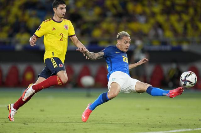 Brazil's Antony connects a shot chased by Colombia's Stefan Medina during a qualifying soccer match for the FIFA World Cup Qatar 2022 in Barranquilla, Colombia, Sunday, Oct. 10, 2021. (AP Photo/Fernando Vergara)
